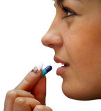 Beautiful Girl Brings To Mouth Capsule Royalty Free Stock Photo