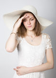 Beautiful girl in broad-brimmed hat posing and expresses different emotions. headache, sadness, fatigue.  Royalty Free Stock Photos