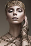 Beautiful girl with a bronze skin, pale makeup and unusual accessories. Art beauty image. Beauty face. Stock Photos