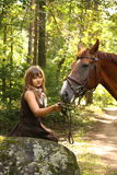 Beautiful girl and brown horse portrait in mysterious forest Stock Photo