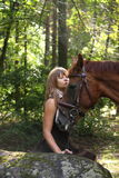 Beautiful girl and brown horse portrait in mysterious forest Royalty Free Stock Photos