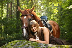 Beautiful girl and brown horse portrait in mysterious forest Royalty Free Stock Images