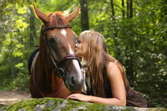 Beautiful girl and brown horse portrait in mysterious forest Stock Photography