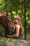Beautiful girl and brown horse portrait in mysterious forest Royalty Free Stock Photography