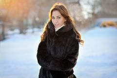 Beautiful girl in brown winter coat on the street Royalty Free Stock Image