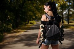 Beautiful girl brunette with backpack behind back in which roller skates Royalty Free Stock Photography
