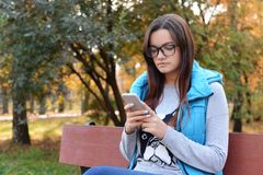 Beautiful girl in glasses sits on a bench and writes and reads S royalty free stock photography
