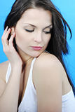 Beautiful girl brunette looks downwards. Beautiful girl brunette with long hair on turn blue background looks downwards Royalty Free Stock Image