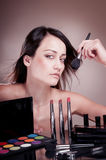Beautiful girl with  brush near the face. Royalty Free Stock Photography
