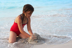 Beautiful girl building a sand castle in the beach. Beautiful caucasian girl building a sand castle in the beach Royalty Free Stock Images