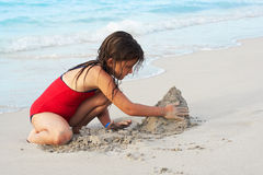 Beautiful girl building a sand castle in the beach. Beautiful caucasian girl building a sand castle in the beach Royalty Free Stock Image