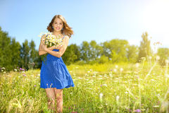 Beautiful girl with bunch of camomiles Stock Image