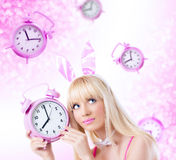 Beautiful girl in bunny ears holding clock Royalty Free Stock Image