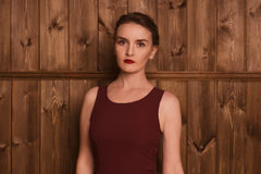 Beautiful girl in a burgundy dress. Beautiful girl beautiful girl in a burgundy dress on a background of a wooden wall Stock Photos