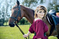 A beautiful girl in a burgundy dress. Is holding a brown horse and looking into the frame stock photography