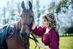 A beautiful girl in a burgundy dress and brown horse. A beautiful girl in a burgundy dress is holding a brown horse andthe girl looks at the horse and talks to royalty free stock image