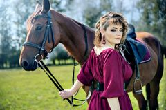 A beautiful girl in a burgundy dress and her horse. A beautiful girl in a burgundy dress is holding a brown horse and looking down stock images