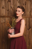 Beautiful girl in a burgundy dress. Holding a vase of flowers Stock Image