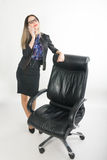 Beautiful girl in a business suit stands next to a leather chair Stock Images