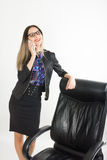 Beautiful girl in a business suit stands next to a leather chair Royalty Free Stock Photos