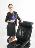 Beautiful girl in a business suit stands next to a leather chair Stock Photo