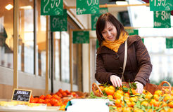 Beautiful girl buying mandarins at market Royalty Free Stock Images