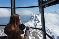 Beautiful girl in the cabin of the cable car, high above the mountains. View from the gondola. Stock Images
