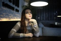 Beautiful girl in a cafe. Having a cup of coffee at a dinner Royalty Free Stock Images