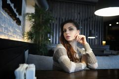 Beautiful girl in a cafe. Having a cup of coffee at a dinner Stock Photo