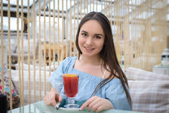 Beautiful girl in a cafe. Beautiful girl in a blue blouse with a glass of mulled wine sitting at a table in a cafe Stock Photo