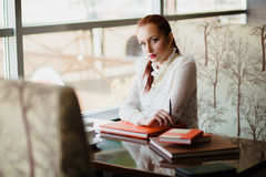 Beautiful girl in the cafe. With books Stock Photography