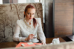 Beautiful girl in the cafe. With books Stock Images