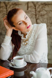 Beautiful girl in the cafe. With books Royalty Free Stock Photography