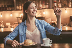 Beautiful girl at the cafe. Beautiful girl is calling a waiter and smiling while sitting at the cafe Royalty Free Stock Image