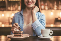 Beautiful girl at the cafe. Cropped image of beautiful girl eating cake and smiling while sitting at the cafe Royalty Free Stock Images