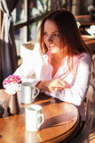 Beautiful girl in a cafe with a cup of coffee Stock Photo