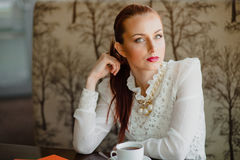 Beautiful girl in the cafe. With a cup of tea Royalty Free Stock Photography