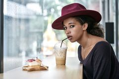 Beautiful girl in cafe. Delightful curly girl drinks a cocktail in a cafe on the windows background. She wears a dark longsleeve with a crimson hat and looks Royalty Free Stock Images