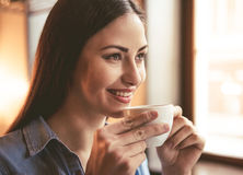 Beautiful girl at the cafe. Beautiful girl is drinking coffee and smiling while sitting at the cafe Stock Photography