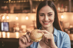 Beautiful girl at the cafe. Beautiful girl is eating sandwich, looking at camera and smiling while sitting at the cafe Royalty Free Stock Photography