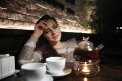 Beautiful girl in a cafe. Having a cup of coffee at a dinner Royalty Free Stock Photos