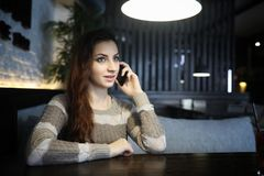 Beautiful girl in a cafe. Having a cup of coffee at a dinner Stock Photography