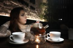 Beautiful girl in a cafe. Having a cup of coffee at a dinner Stock Photos
