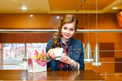 Beautiful girl in the cafe opens white gift box Stock Images
