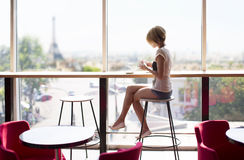 Beautiful girl in a cafe in Paris. Young beautiful girl with sitting near the panaramic window in a cafe in Paris. Eiffel Tower. Sunny day in restoran Stock Image
