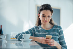 Beautiful girl at the cafe. Sitting at the counter and texting with her phone Stock Photography