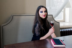 Beautiful girl in the cafe. A beautiful girl sitting in the cafe with wine Royalty Free Stock Image