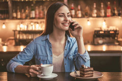 Beautiful girl at the cafe. Beautiful girl is talking on the mobile phone and smiling while sitting at the cafe Royalty Free Stock Photos