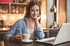 Beautiful girl at the cafe. Beautiful girl is using a laptop, drinking coffee, looking at camera and smiling while sitting at the cafe Stock Photo