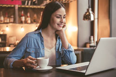 Beautiful girl at the cafe. Beautiful girl is using a laptop, drinking coffee and smiling while sitting at the cafe Stock Photo